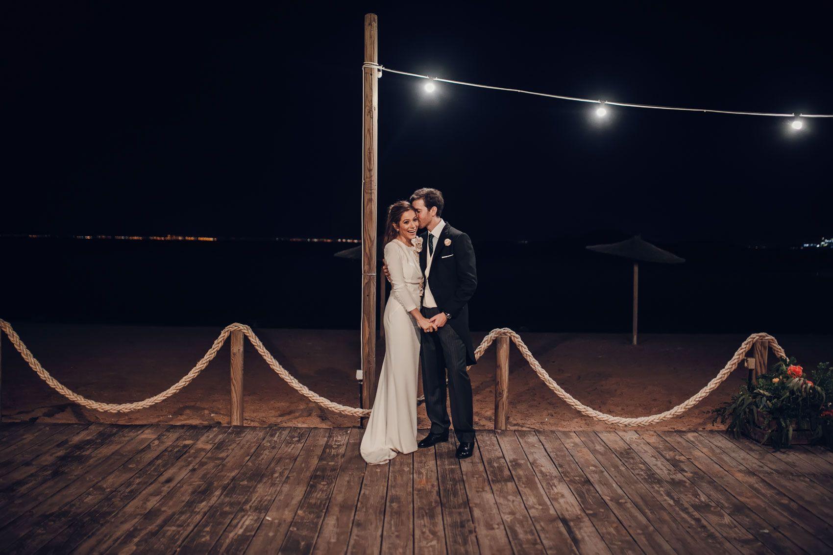pareja novios beso playa paseo madera