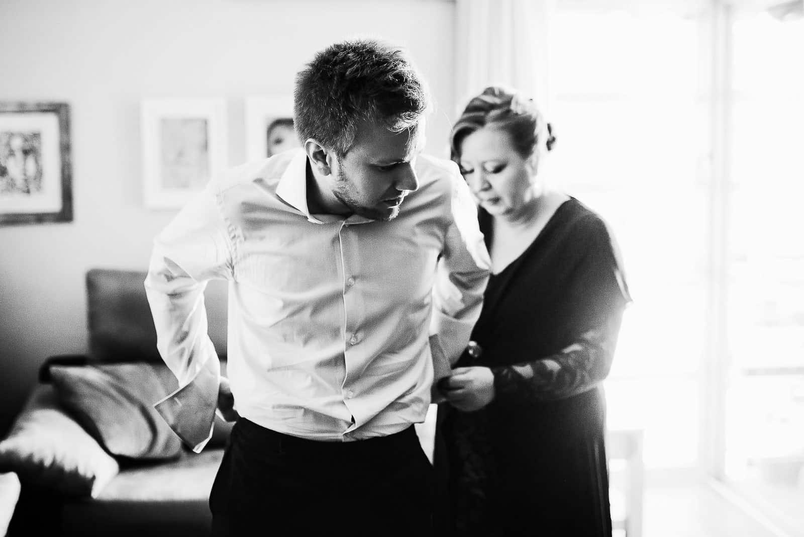 novio vistiendose traje boda