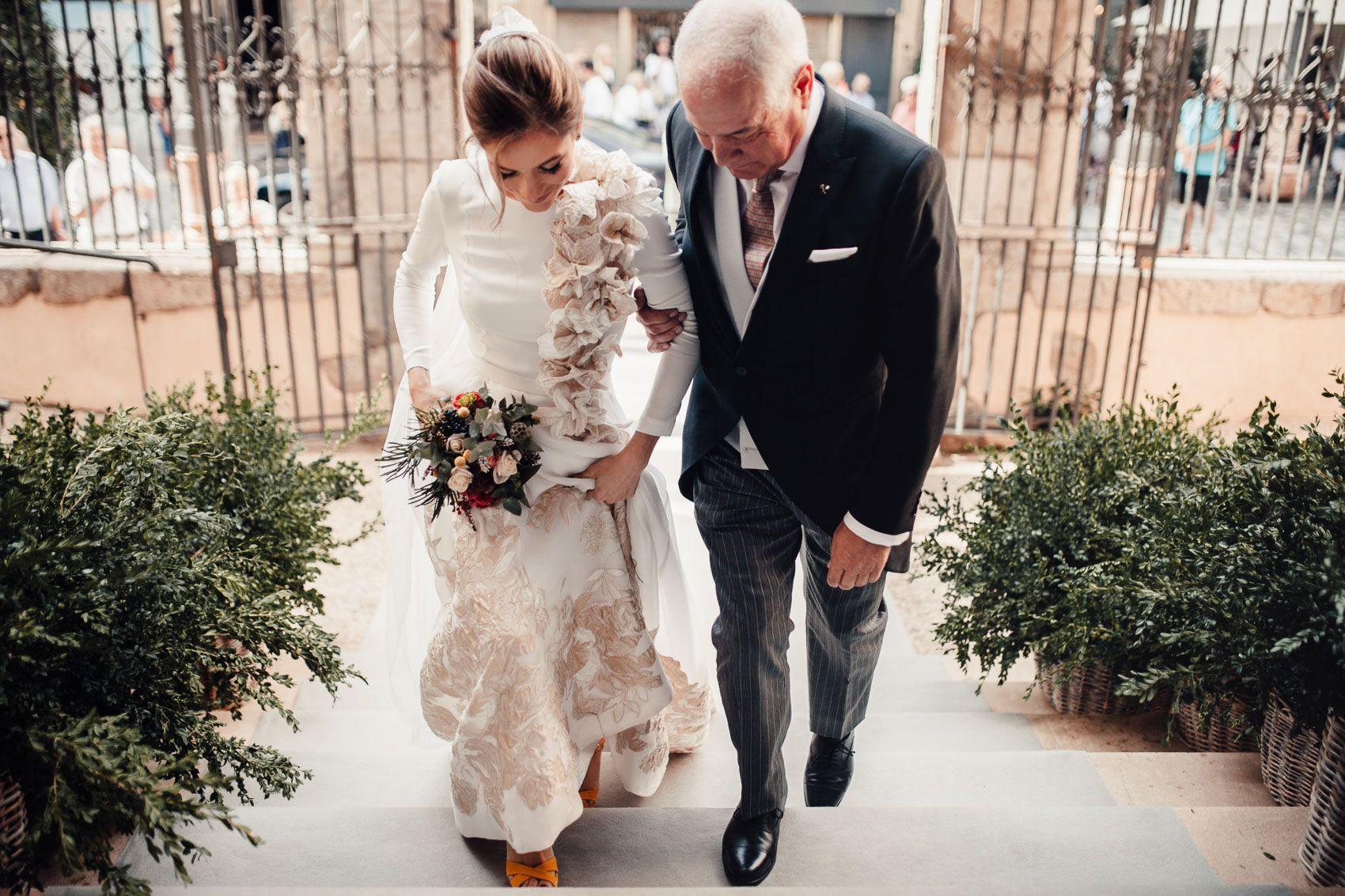 Novia subiendo las escaleras con su padre con vestido de Fernando Claro