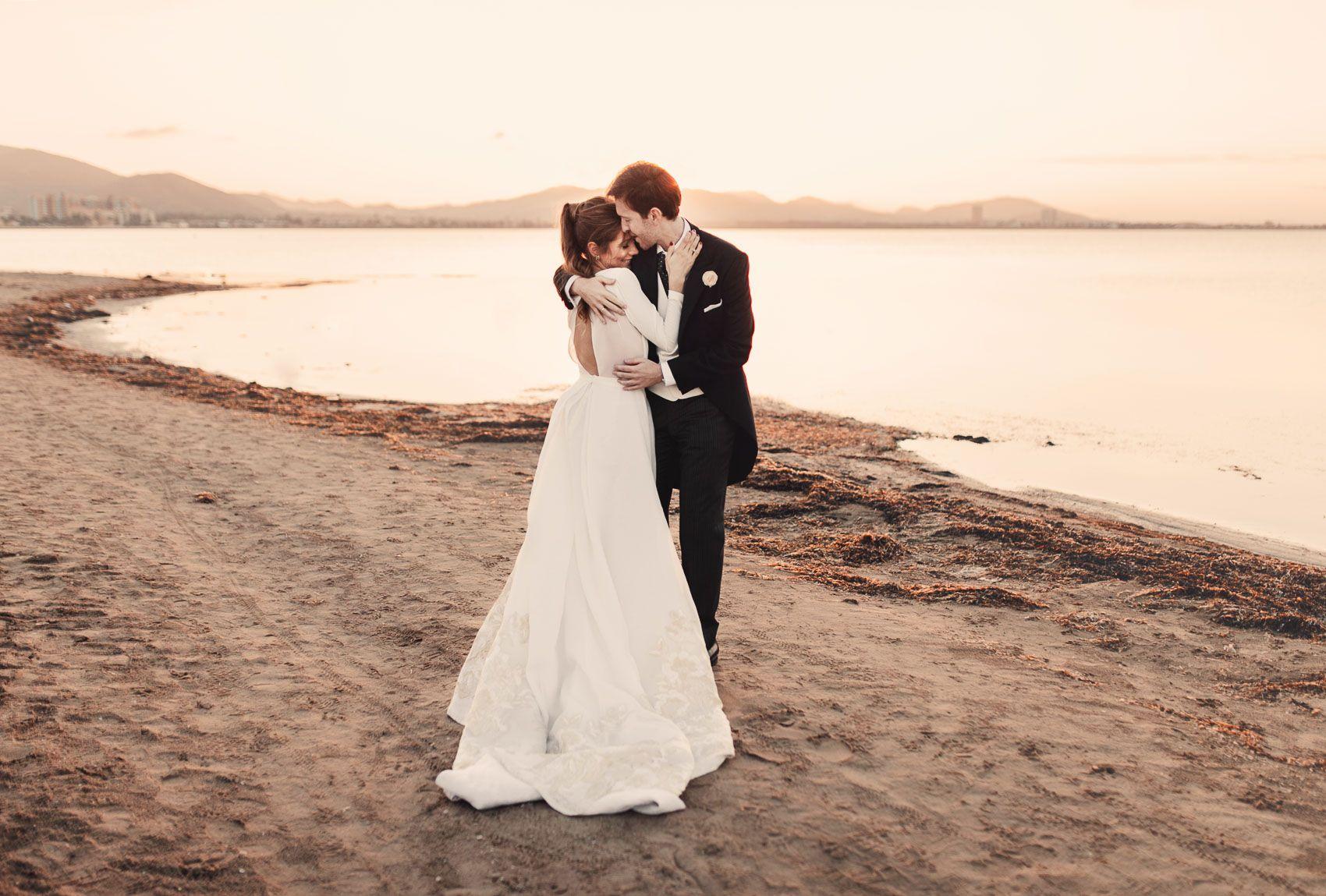 Novios abrazandose atardecer Mar Menor vestido novia Fernando Claro