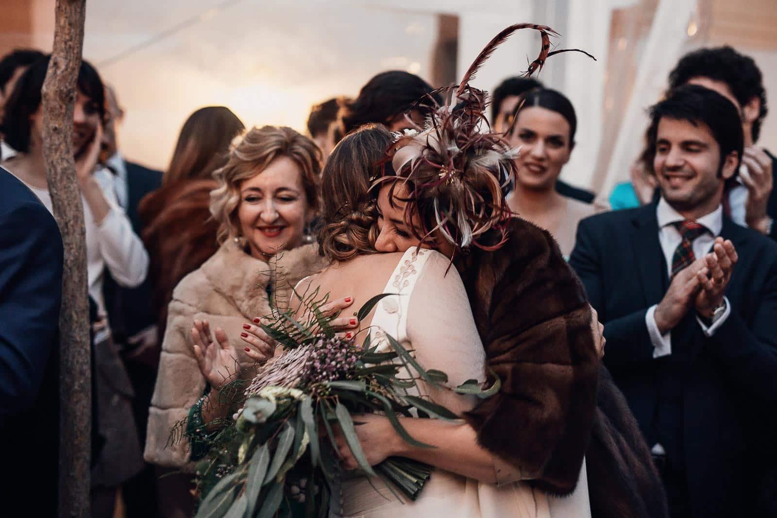 abrazo novia invitados tocado ramo flores abrigos