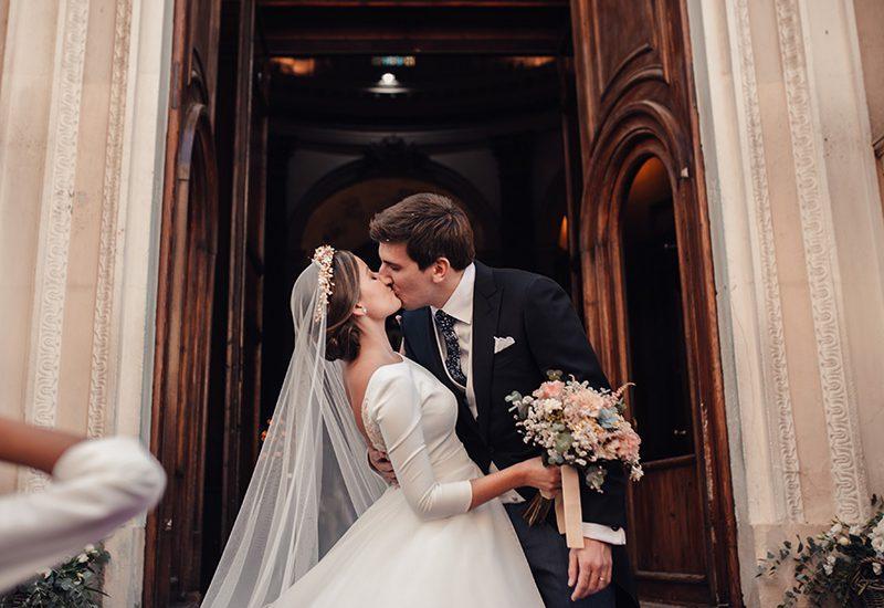 Beso romantico pareja saliendo de la iglesia vestido de Novia rubén hernandez
