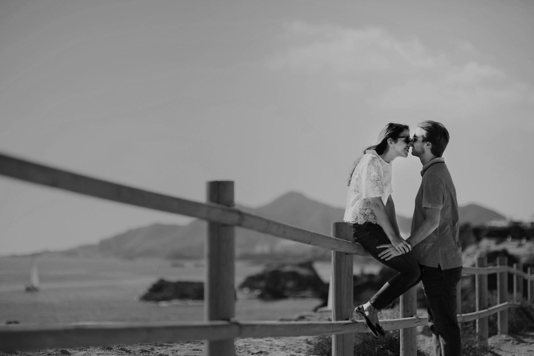 pareja beso valla madera playa